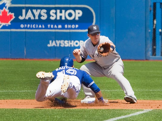 Toronto Blue Jays' Jose Bautista is picked off at second base as New York Yankees second baseman Stephen Drew takes the throw during first inning baseball action in Toronto, Sunday, Aug. 16, 2015. (Fred Thornhill/The Canadian Press via AP)