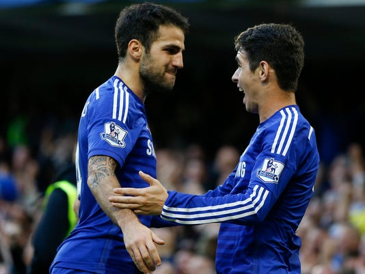 Chelsea's Oscar, right, celebrates scoring a goal with team member Cesc Fabregas during the English Premier League soccer match between Chelsea and Queens Park Rangers at Stamford Bridge Stadium in London, Saturday, Nov. 1, 2014. (AP Photo/Kirsty Wigglesworth)