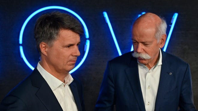 The CEO of German auto giant Daimler AG Dieter Zetsche (R) and CEO of German carmaker BMW Harald Krueger speak to TV reporters after they presented the merger of their car sharing activities on February 22, 2019 in Berlin.