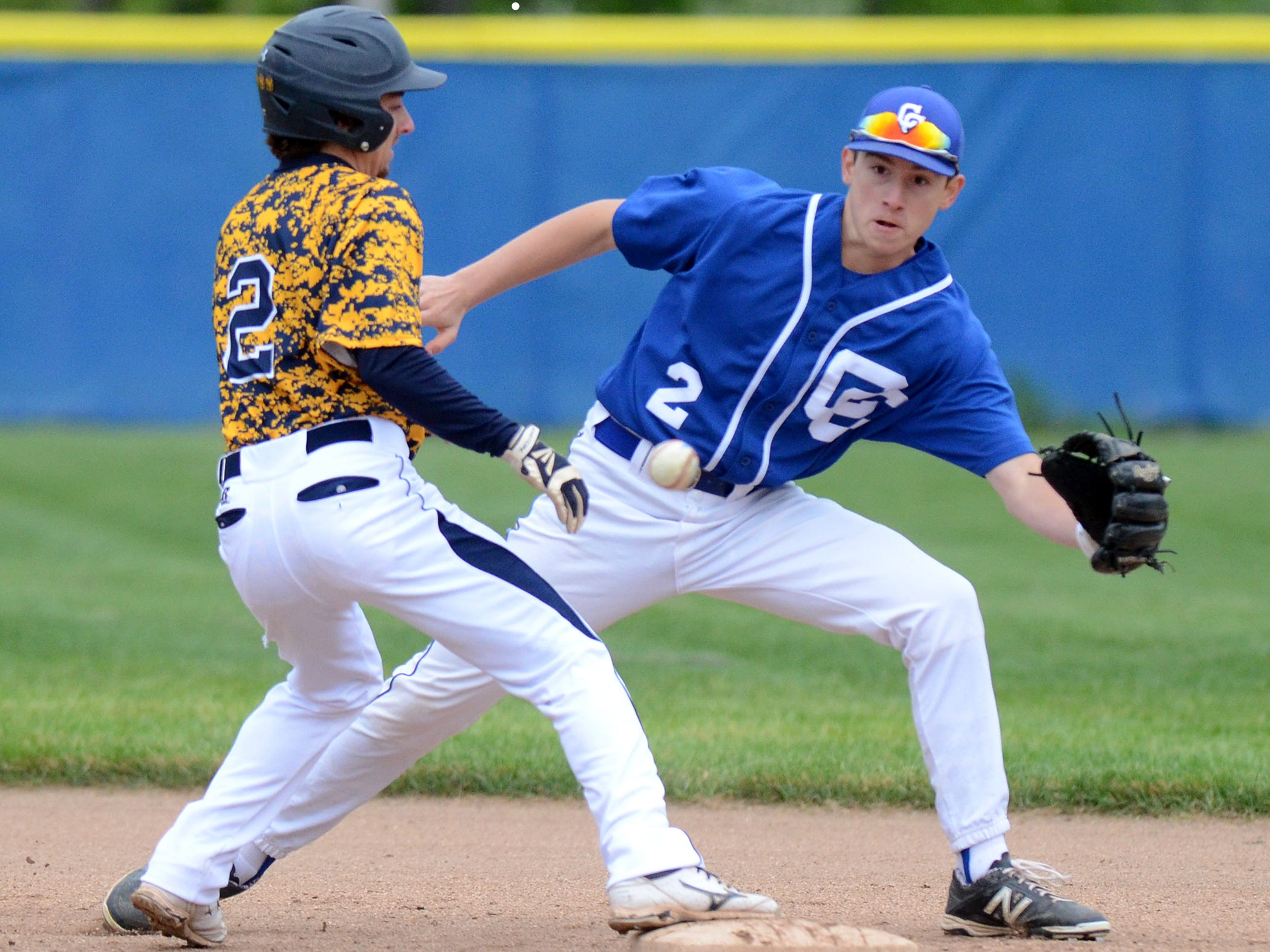 Catholic Central shortstop Nick Marcon (right) tries to keep an eye on a pick-off attempt at second base during a May 19 double-header vs. South Lyon.