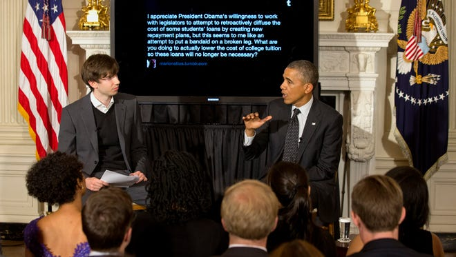 President Barack Obama answers a question during a Tumblr forum, moderated by Tumblr founder and CEO David Karp, left, Tuesday, June 10, 2014, in the State Dining Room of the White House in Washington.