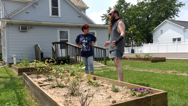 Karen Moysi, left, and Jon Slater III talk about the community garden they've started on West Walnut Street in Lancaster.