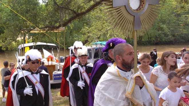 Rev. Michael Champagne carries the Blessed Sacrament to an outdoor altar after arriving by boat from Leonville. Hundreds of people recited the rosary Saturday on the banks of Bayou Teche.