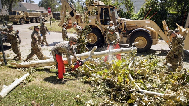 Sgt. Chris Peterson (left) of Dyersville, Iowa, and Staff Sgt. Steven Russell of Ankeny, Iowa, with the Alpha Co., 224th Brigade Engineer Battalion of the Iowa National Guard use chainsaws to cut limbs off a downed tree as cleanup continues along 30th St. SE in southeast Cedar Rapids, Iowa, on Saturday. About 100 engineers from the Fairfield, Iowa-based unit are assisting utility companies with debris removal so line work can progress.