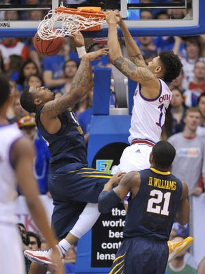 Kansas Jayhawks guard Kelly Oubre Jr. (12) dunks the ball as West Virginia Mountaineers forward Elijah Macon (45) defends during the first half at Allen Fieldhouse.