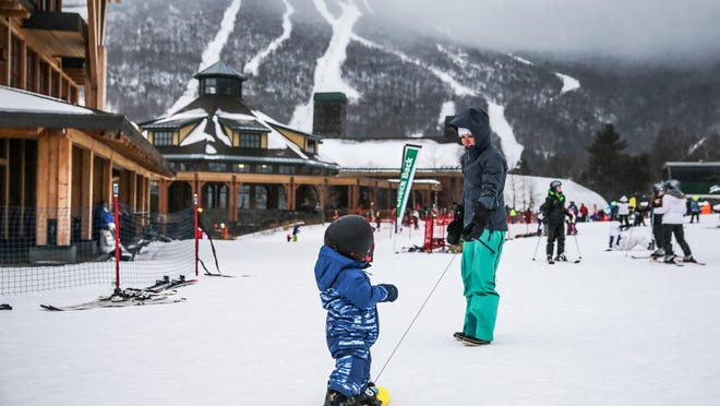 Andrea Elias of Montreal tows her 15-month-old son, Noah, at Stowe Mountain Resort using a snowboard teaching tool called a Riglet. The Riglet was invented by Jeff Boliba, a Burton executive from Williston.
