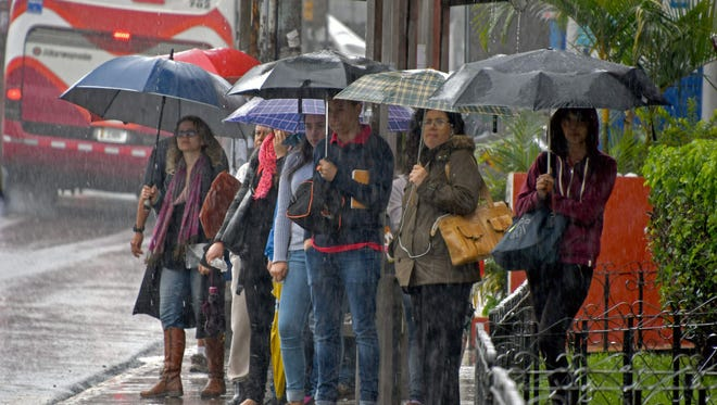 People wait at a bus stop during a downpour caused by Tropical Storm Nate in Cartago, Costa Rica, on Oct. 5, 2017.