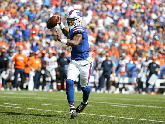 Bills quarterback Tyrod Taylor throws while rolling