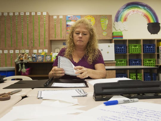 Tammy Morrison, a first- grade teacher at Bayshore Elementary School in North Fort Myers, builds folders as she prepares for the upcoming school year.