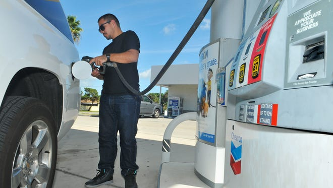 Libra Garcia of Los Angeles  fills up his sport utility vehicle at the Chevron gas station on Courtenay Parkway on Merritt Island.