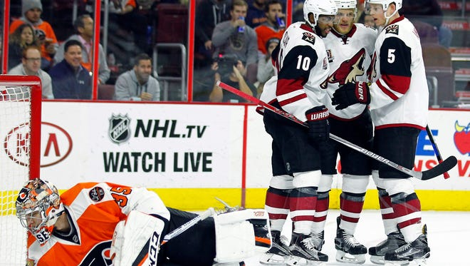 Philadelphia Flyers goalie Steve Mason looks back for the puck as the Arizona Coyotes' from the left, Anthony Duclair, Jamie McGinn and Connor Murphy celebrate McGinn's goal during the first period of an NHL hockey game, Thursday, Oct. 27, 2016, in Philadelphia.