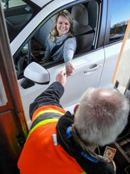 Jessica Smith of Anderson pays Lee Currens, toll collector,