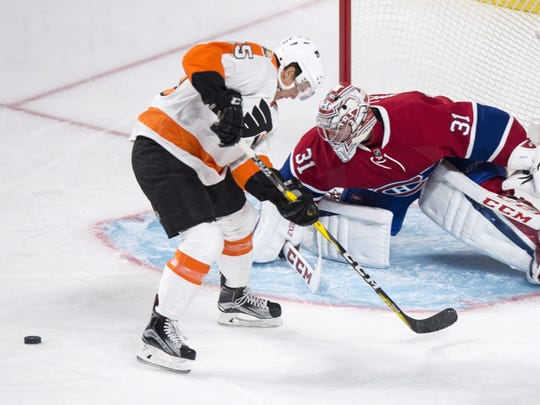 Philadelphia Flyers center Nick Cousins (left) loses the puck as he skates toward Montreal Canadiens goalie Carey Price during the first period of Monday's game.
