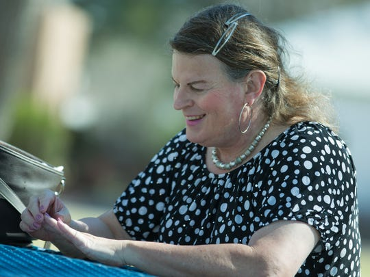 Jodi Wenneborg, 52, a transgender woman, looks at her manicure while speaking with a reporter during an interview at Pioneer Women's Park.