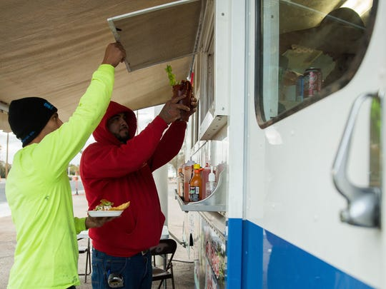 Eddie Ruiz, right, and Steven Espino, left, pick up a food order from Mariscos El Güero seafood truck parked off of North Solano Drive on Wednesday Dec. 6, 2017. On Thursday, the high temperature is expected to be in the 30s, and light snow is possible.