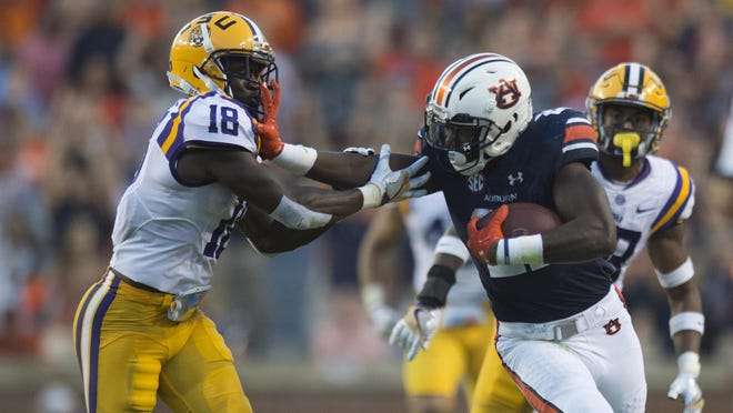 Auburn running back Kerryon Johnson stiff arms LSU cornerback Tre'Davious White.