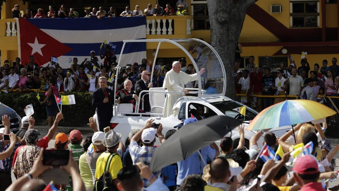 Pope Francis waves from his popemobile as he travels Monday to the Plaza of the Revolution to celebrate Mass in Holguin, Cuba.