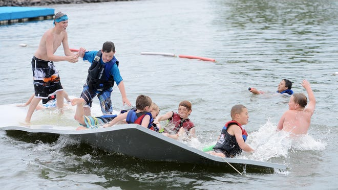 Campers play on a floating pad Tuesday at Camp OnAqua at Catfish Bay.