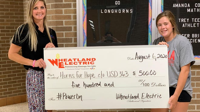 Amy Wickwar, a specialist with Jobs for America's Graduates-Kansas, left, and Blair Holliday, a senior at Holcomb High School who serves as JAG-K president, pose to accept a $500 donation for Horns for Hope, c/o USD 363.