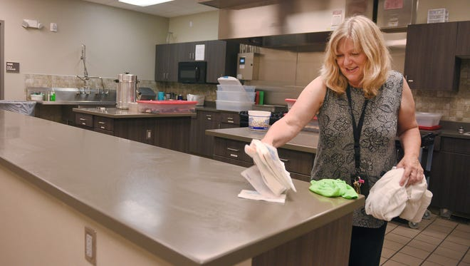Weekend Supervisor Lynn Haagenson cleans the kitchen after lunch Monday at the Bishop Dudley Hospitality House in Sioux Falls.