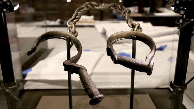 A pair of slave shackles are on display in the Slavery and Freedom Gallery in the Smithsonian's National Museum of African American History and Culture during the press preview on the National Mall last week in Washington, DC. Filled with exhibits and artifacts telling the story of the first Africans in the United States and their descendants, the 400,000-square-foot museum will open to the public on September 24.