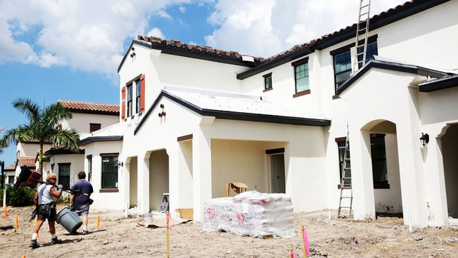 Construction workers work on homes in Livingston Lakes by WCI Communities in Naples on Thursday, Sept. 22, 2016.