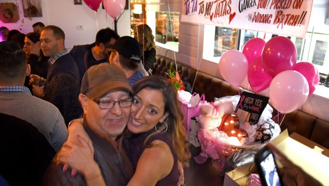 """Andy Sealy, right, dances with her father, John Sealy, at a farewell party March 5, 2017, she calls """"Ta-Ta to My Tatas."""" She is getting a double mastectomy after finding her tumor during a self exam, and wants to encourage friends to also do self-screening."""