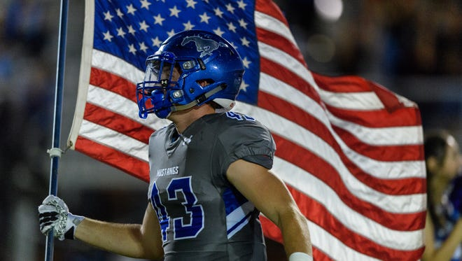Dobson Seth Stratman (#43) carries the American flag as the they take the field before their high school football game on Friday, Sept. 15, 2017, at Dobson High School in Mesa, Ariz.