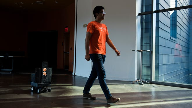 Clemson automotive engineering PhD student Longxiang Guo is followed by a Smart Shopping Companion Robot prototype at the Carroll A. Campbell Jr. Graduate Education Center on Monday, Oct. 30, 2017.