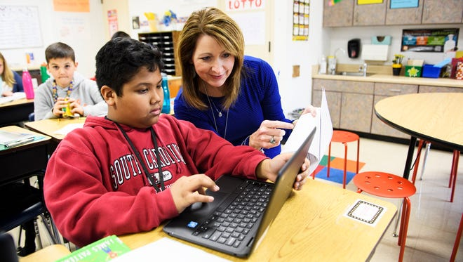 Fourth grade teacher Suzanne Billings helps Jacob Ortiz, 10, with his classwork at Plain Elementary School on Thursday, March 8, 2018.