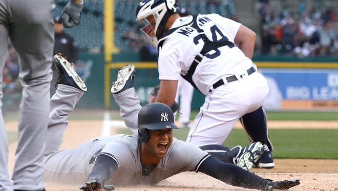 Aaron Hicks #31 of the New York Yankees slides into home plate next to James McCann #34 of the Detroit Tigers for a second inning inside the park home run at Comerica Park on April 13, 2018 in Detroit.