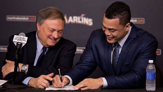 Giancarlo Stanton signs his new contract with the Miami Marlins as owner Jeffrey Loria looks on during a press conference at Marlins Park on Wednesday.