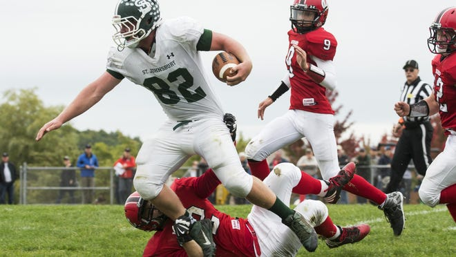 St. Johnsbury's Brodie Talbot (82) is tackled by CVU's Jake Bortnick (32) during the high school football game between the St. Johnsbury Hilltoppers and the Champlain Valley Union Redhawks at CVU high school on Saturday afternoon October 1, 2016 in Hinesburg. (BRIAN JERKINS/for the FREE PRESS)