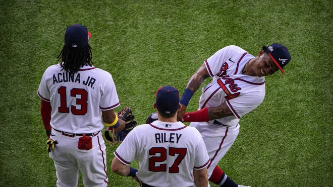 Atlanta Braves right fielder Ronald Acuna Jr. (13), left fielder Austin Riley (27) and center fielder Cristian Pache (14) wait out a pitching change during the third inning against the Los Angeles Dodgers in game three of the 2020 NLCS at Globe Life Field.
