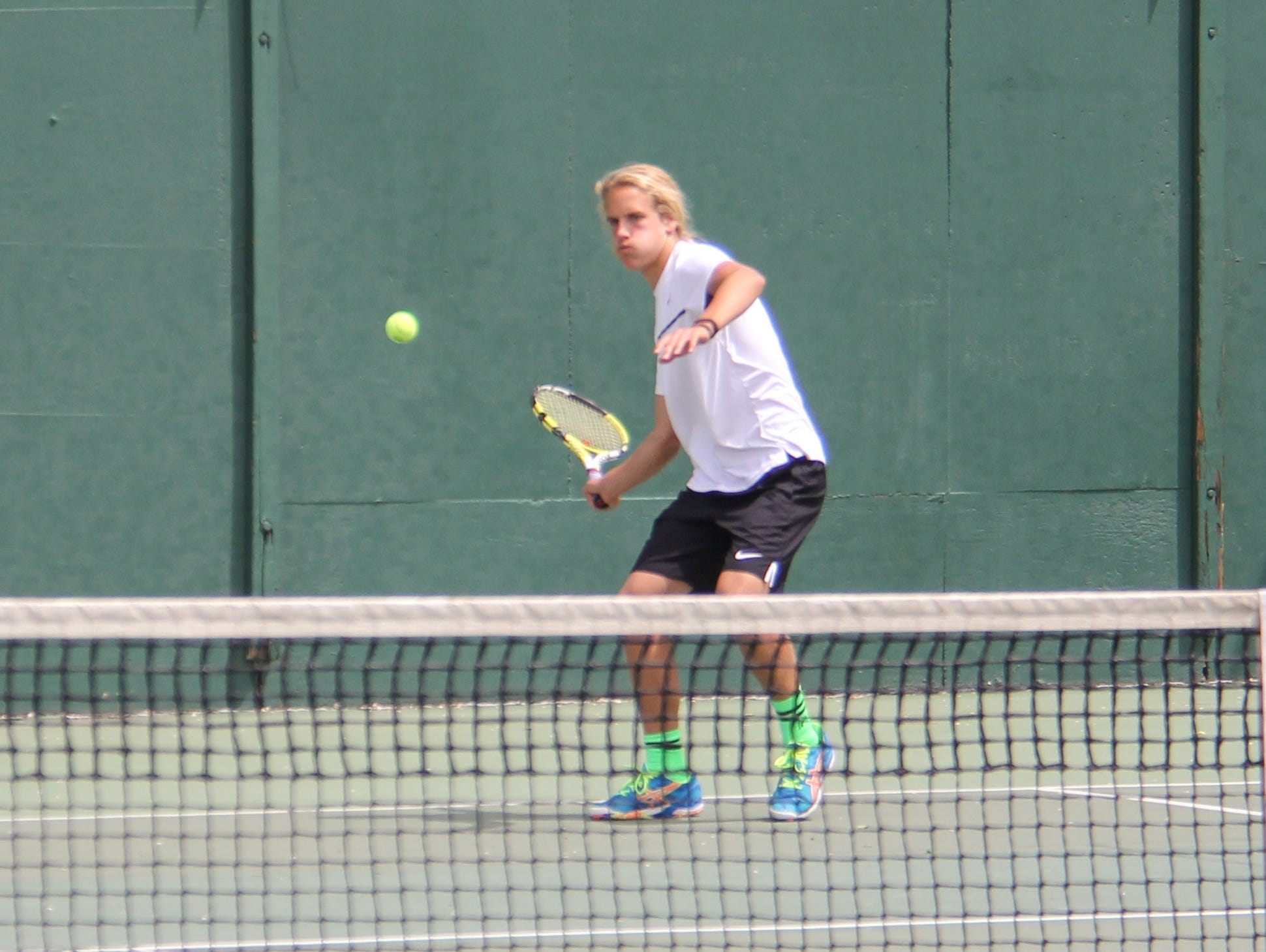 Austin Hardy prepares to hit a forehand during a doubles match last season.