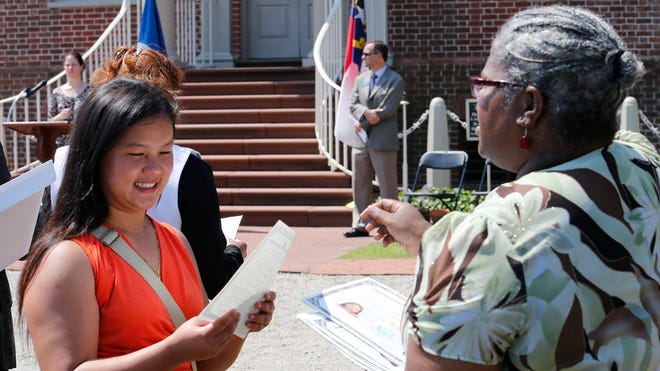 Lay Na, formerly of Myanmar, receives her certificate of citizenship during a naturalization ceremony June 11 in New Bern, N.C. Fifty people took the oath of citizenship. New Census figures show that more Asians are immigrating to the USA than Hispanics.