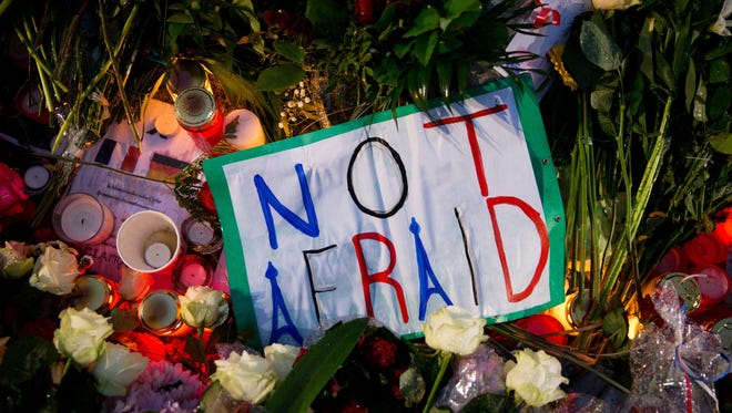Flowers and signs pile up at the French Embassy in Berlin on Sunday.