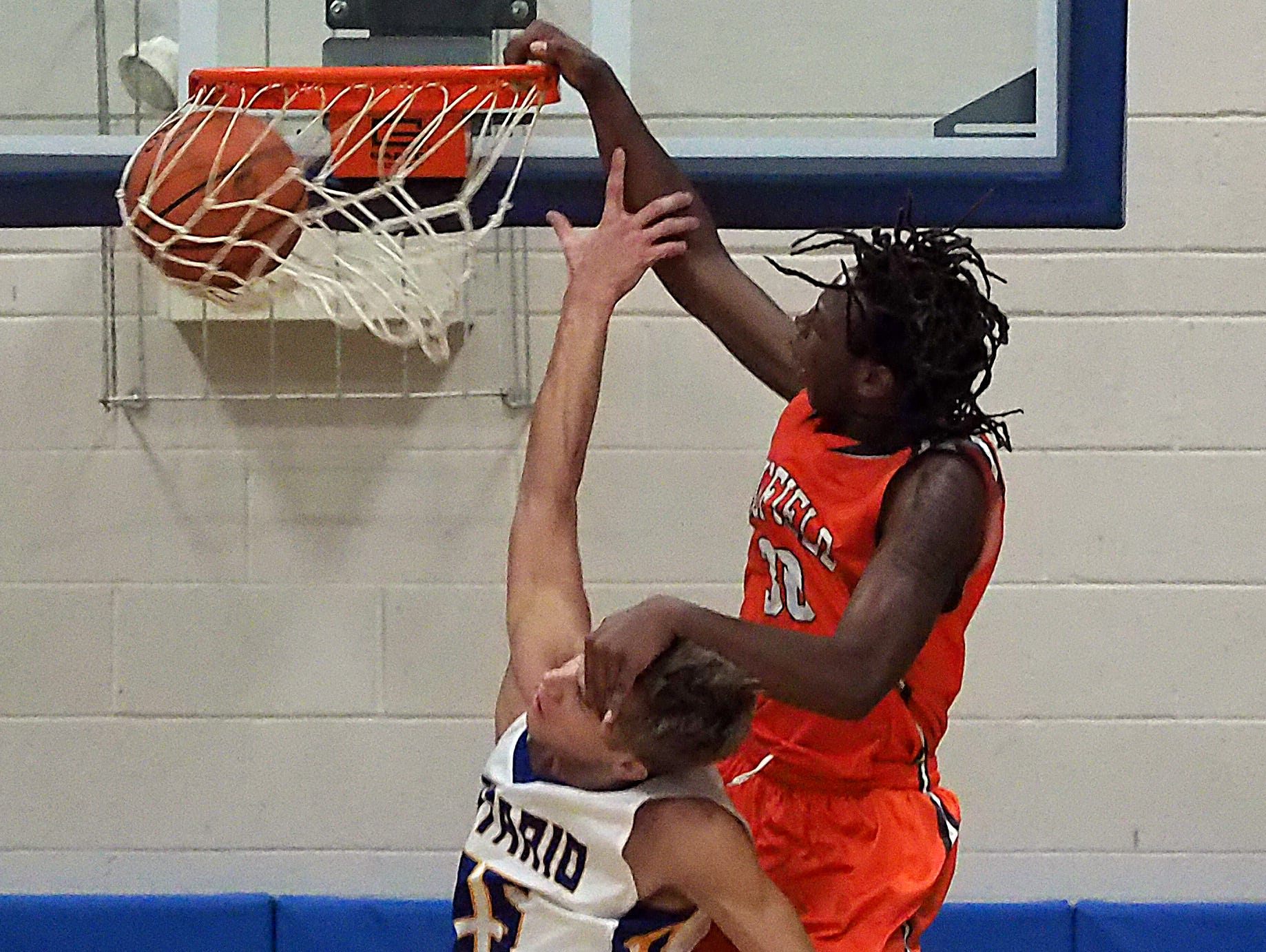 Mansfield Senior's Mario Young dunks over Ontario's Corey Thomas and draws the foul during their game Friday night at Ontario High School.
