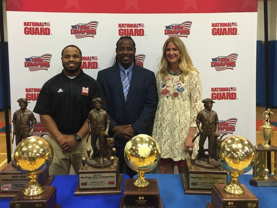 Madison Central head soccer coach Cecil Hinds (center) is joined by assistants Leonard Swilley and Ashley Davis after being presented trophies from MaxPreps on its annual tour of champions. Madison Central's girls and boys team won Class 6A state titles and finished ranked No. 1 and 3, respectively, in the nation.
