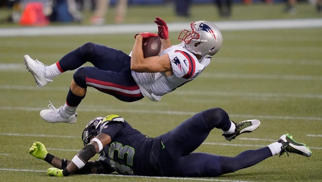 Patriots wide receiver Julian Edelman comes down with a catch over Seahawks strong safety Jamal Adams during Sunday night's second half.