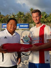 Quality Distributors FC's Jan-Willem Staman poses with the 2016 Land Shark Beach Soccer League Golden Boot trophy, presented by Guam Football Association men's administrator Samuel San Gil, in an awards ceremony following the league's championship match Sunday at the GFA National Training Center beach soccer court.