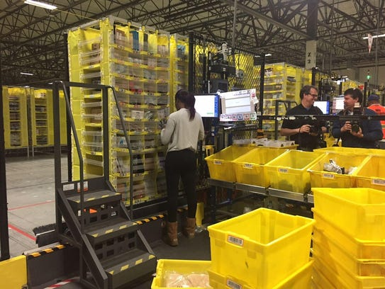 Workers at Amazon Carteret prepare orders for shipment