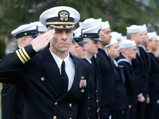 Cmdr. Kelly Laing, commanding officer of the USS Maine, salutes during the national anthem and presentation of colors at a memorial Dick Turpin on Friday at Ivy Green Cemetery in Bremerton. Turpin served on a famous, previous USS Maine -- the one that exploded in Havana harbor in 1898, leading to the Spanish-American War.