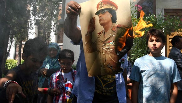 Demonstrators set fire to a poster of Libyan leader