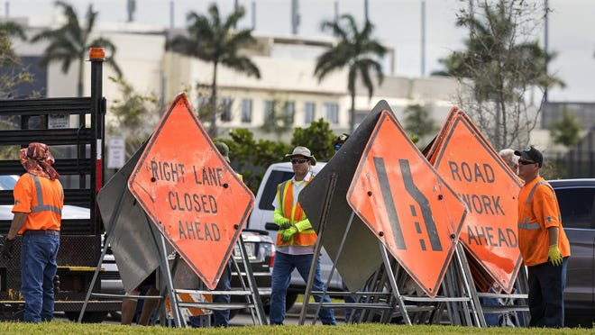 Palm Beach County workers  set up for drive-thru coronavirus testing at The FITTEAM Ballpark of the Palm Beaches in West Palm Beach on Sunday morning. An additional 1,000 testing kits arrived overnight which will allow testing to continue this week.