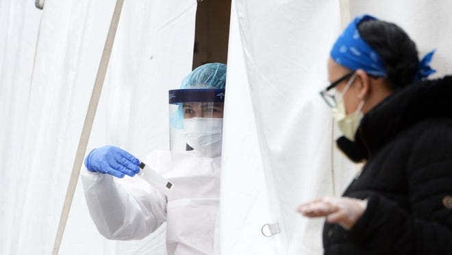 A Brockton Neighborhood Health Center employee, wearing full personal protective equipment, peers out from a coronavirus testing tent outside the downtown Brockton facility, Wednesday, April 22, 2020. The health center is one of 12 in Massachusetts expanding its testing through a state partnership.