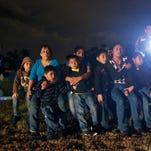 Group of immigrants from Honduras and El Salvador are stopped at U.S.-Mexico border in June 2014. The number of families caught crossing together this October tripled from October 2014.