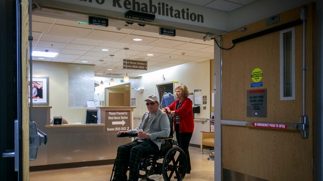 Loretta Baker wheels her son Darin out of the rehab center at Barrow Neurological Institute of St. Joseph's Hospital and Medical Center.