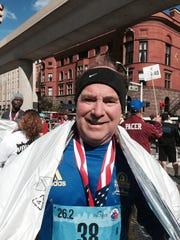 Mark Bauman, 65, of Flushing beams as he finishes his 38th consecutive Detroit marathon 2015.