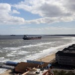 Waves crash on to the beach Wednesday, near where the 751-foot bulk carrier Ornak, lower left, ran aground Tuesday night in the lower Chesapeake Bay, in Virginia Beach. There were no reports of injuries, damage or pollution from the grounding, and the vessel was not blocking other water traffic, said Coast Guard spokesman Petty Officer First Class Brandyn Hill.
